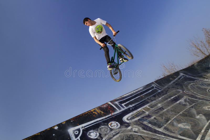 Young bmx bicycle rider. Bicycle rider in the air royalty free stock images