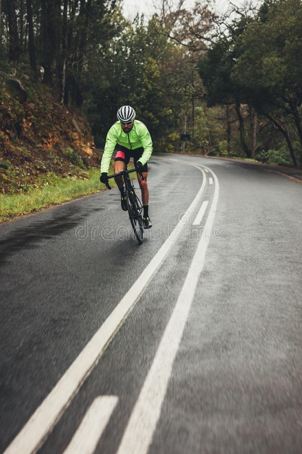 Bicycle rider with bike on wet asphalt road. Bicycle rider riding bike on wet asphalt road in countryside. Man cycling outdoors on empty long road through forest royalty free stock photos