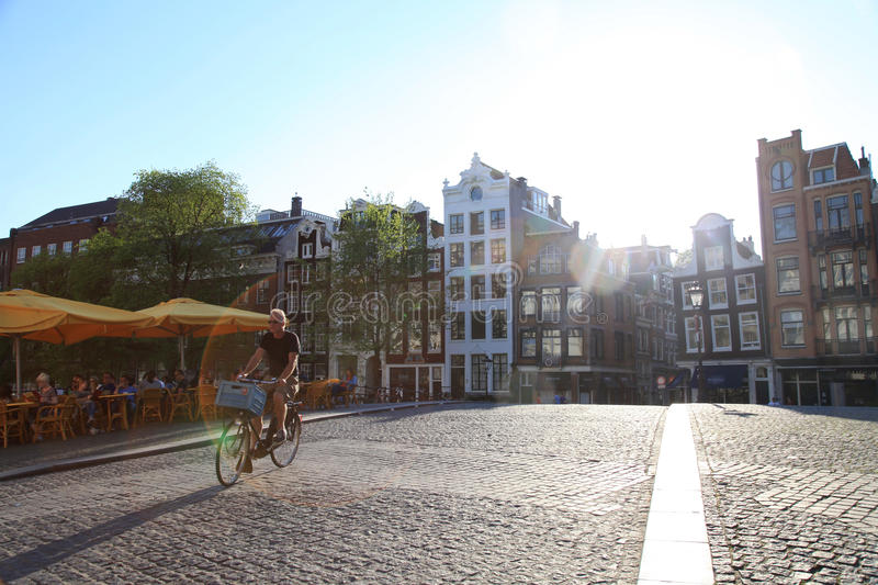 Bicycle rider on cobblestone bridge in the afternoon sunlight, A. AMSTERDAM, NETHERLANDS - MAY 8, 2016: Street scene with bicycle rider on cobblestone bridge in royalty free stock photography