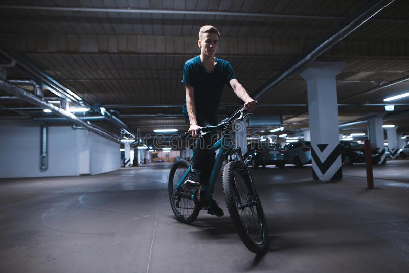 Bicycle rider rides on an underground parking lot. cyclist rides in an underground parking lot stock image
