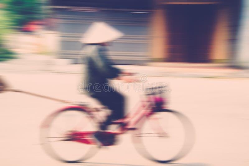 Bicycle rider in vietnam (Motion Blur). Blurred Woman rider in vietnam (motion in vietname stock photo