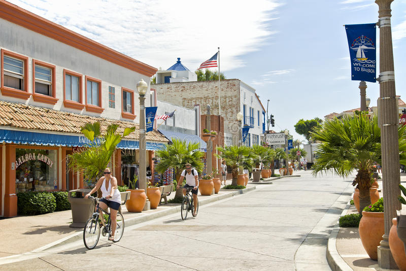 Bicycle Riders, Newport Beach, California. Two people are enjoying their vacation, riding their bikes down a main street lined with retail stores and potted royalty free stock images