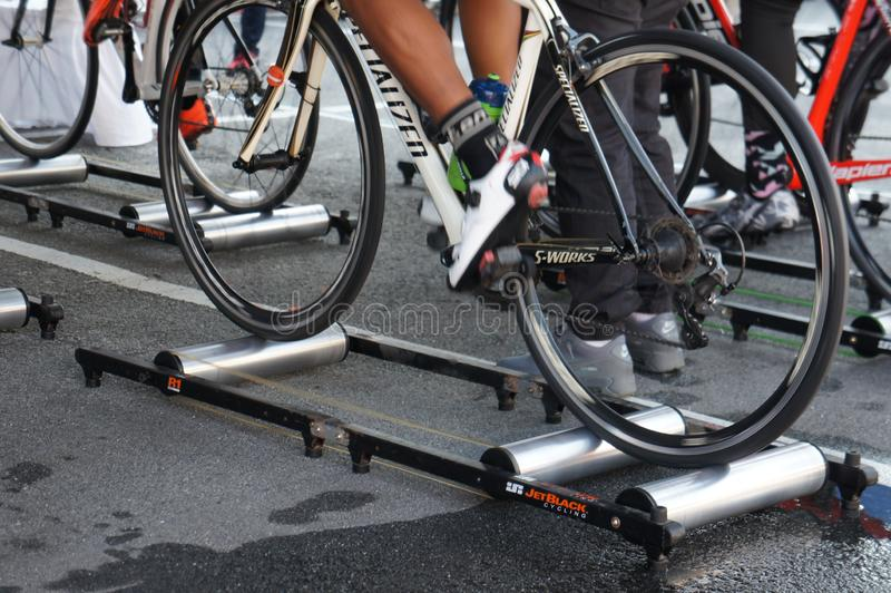 Bicycle riders are using the cycling roller trainer before the race begins. KUALA LUMPUR, MALAYSIA -APRIL 18, 2015: Bicycle riders are using the cycling roller royalty free stock photos