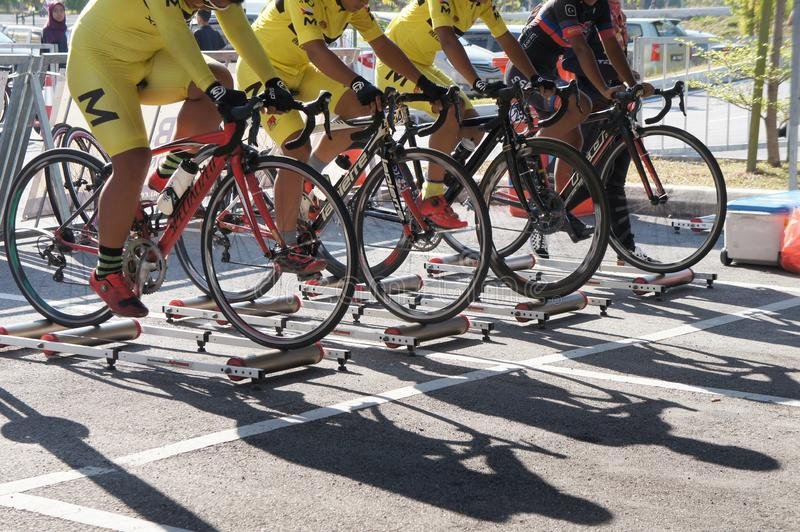 Bicycle riders are using the cycling roller trainer before the race begins. KUALA LUMPUR, MALAYSIA -APRIL 18, 2015: Bicycle riders are using the cycling roller royalty free stock images