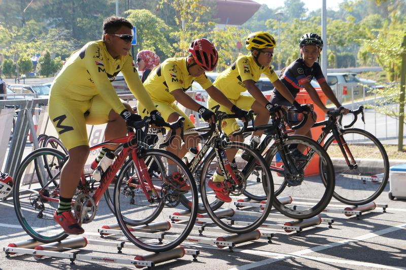 Bicycle riders are using the cycling roller trainer before the race begins. KUALA LUMPUR, MALAYSIA -APRIL 18, 2015: Bicycle riders are using the cycling roller royalty free stock image