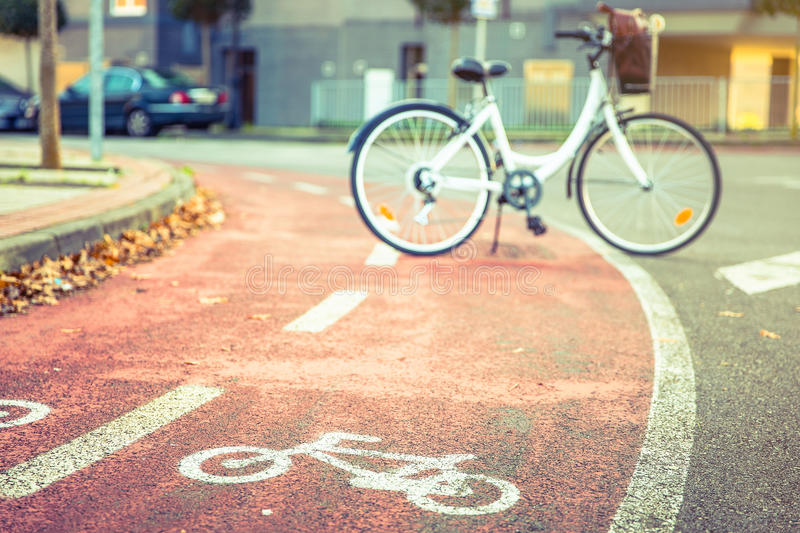 Bicycle road symbol over street bike lane with. Bicycle road symbol over a street bike lane in autumn with white bicycle on the background stock image
