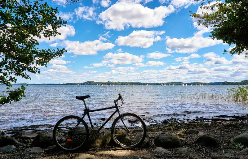 Bicycle at Schwerin lake with sailing yacht race in the background. Mecklenburg-Vorpommern, Germany stock images