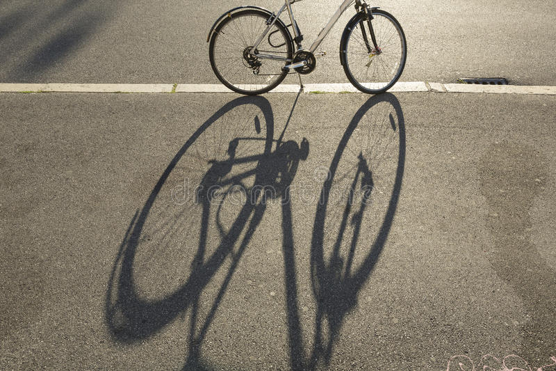 Bicycle and shadow. Shadow of bicycle on the street stock photography