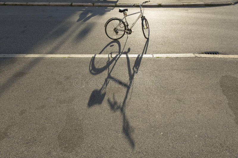 Bicycle and shadow. Shadow of bicycle on the street stock images