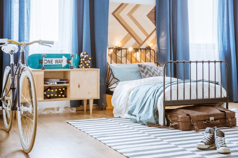 Bicycle and skateboard in bedroom. Blue and white bicycle and skateboard in teenager`s bedroom interior with black, metal bed stock image