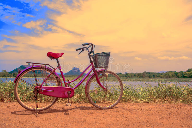 The bicycle stands on a village road at Thalkote lake near Sigiriya. Renting a bicycle and cycling around Sigiriya village is the most popular way among the stock photos