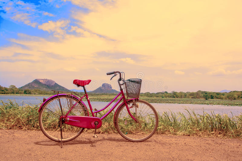 The bicycle stands on a village road at Thalkote lake near Sigiriya. Renting a bicycle and cycling around Sigiriya village is the most popular way among the stock photography
