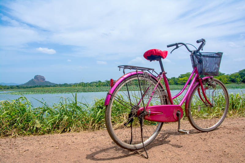 The bicycle stands on a village road at Thalkote lake near Sigiriya. Renting a bicycle and cycling around Sigiriya village is the most popular way among the stock images