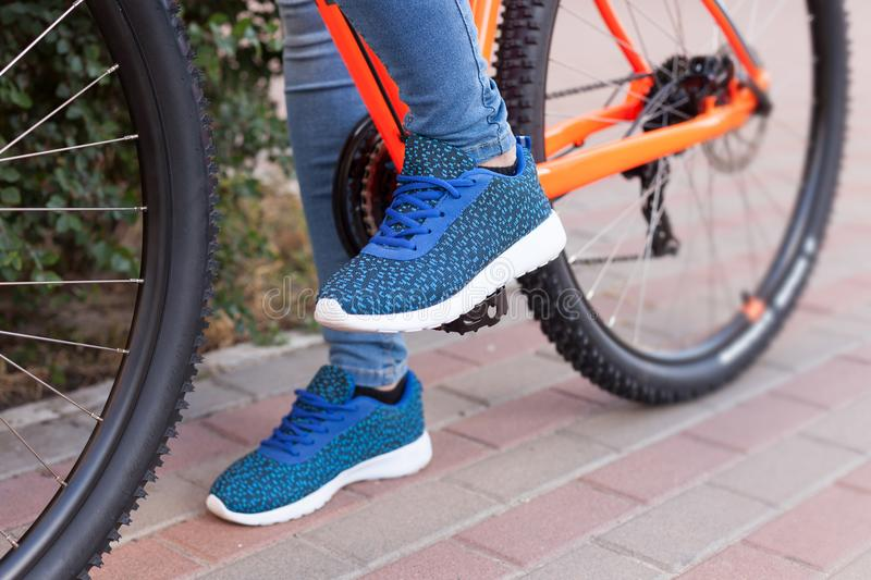 The girl put her foot on the bicycle pedal. A bicycle element on a street background. royalty free stock photography