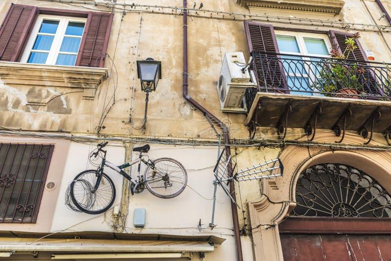 Bicycle a suspensão em uma parede velha em Palermo, Sicília, Itália imagem de stock royalty free