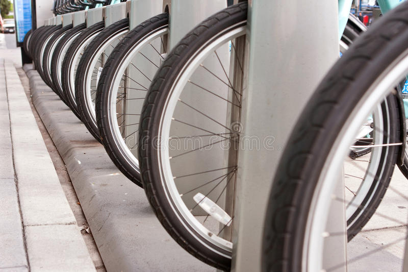 Bicycle Tires Are Lined Up In A Uniform Row. Bicycle tires lined up at an outdoor bike rental station illustrate symmetry and uniformity stock image