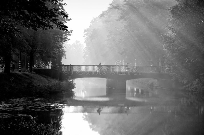 Bicycle to school. Unidentified dutch schoolkids in black and white on their way to school on the bicycle, biking over a bridge in beautiful sunlight in the stock photos