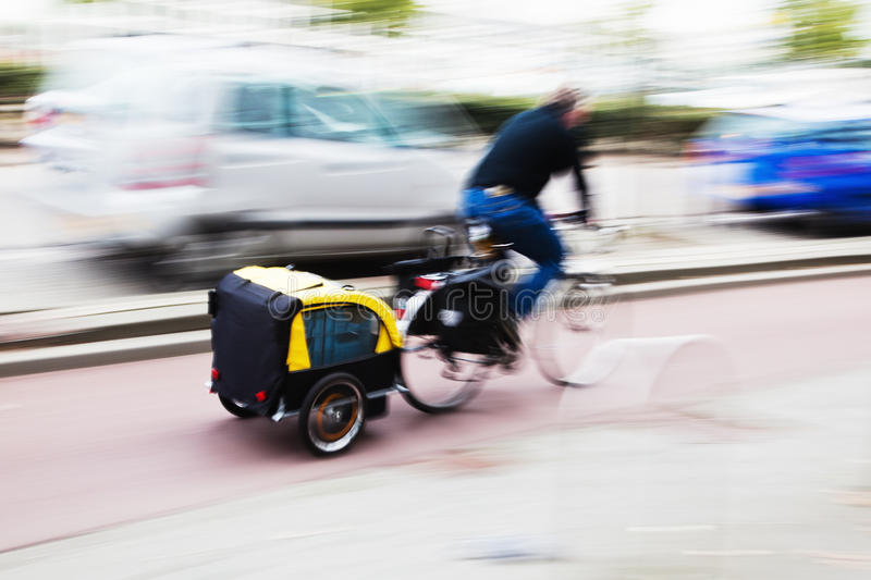 Bicycle with trailer. Man riding a bicycle in city traffic, having a trailer at the bike royalty free stock images