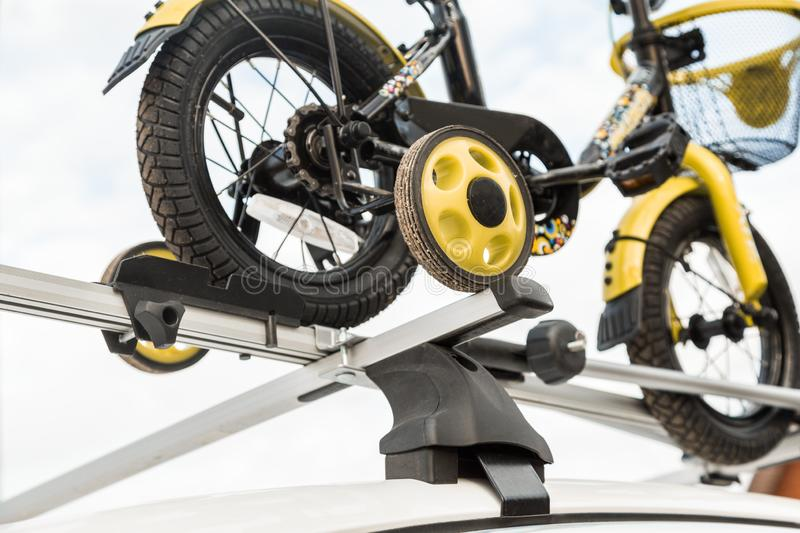 Bicycle transport - a children`s bicycle on the roof of a car against the sky in a special mount for cycling. The. Decision to transport large loads and travel royalty free stock photo