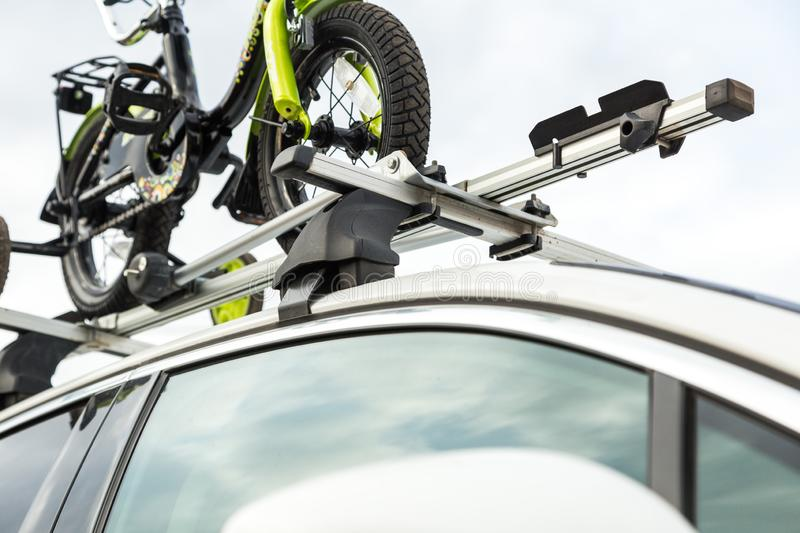 Bicycle transport - a children`s bicycle on the roof of a car against the sky in a special mount for cycling. The. Decision to transport large loads and travel royalty free stock images