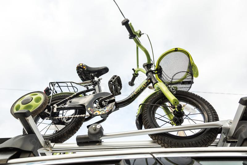 Bicycle transport - a children`s bicycle on the roof of a car against the sky in a special mount for cycling. The. Decision to transport large loads and travel stock photography