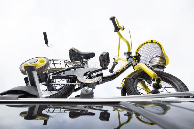 Bicycle transport - a children`s bicycle on the roof of a car against the sky in a special mount for cycling. The. Decision to transport large loads and travel stock images