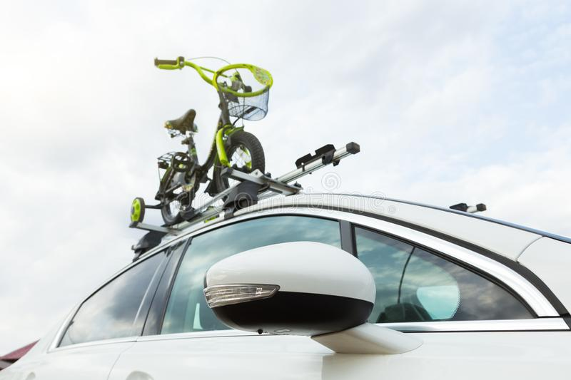Bicycle transport - a children`s bicycle on the roof of a car against the sky in a special mount for cycling. The. Decision to transport large loads and travel royalty free stock image