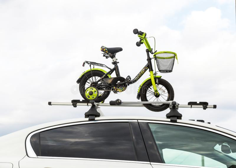 Bicycle transportation - a children`s bicycle on the roof of a car against the sky in a special mount for cycling. The. Bicycle transport - a children`s bicycle stock photo