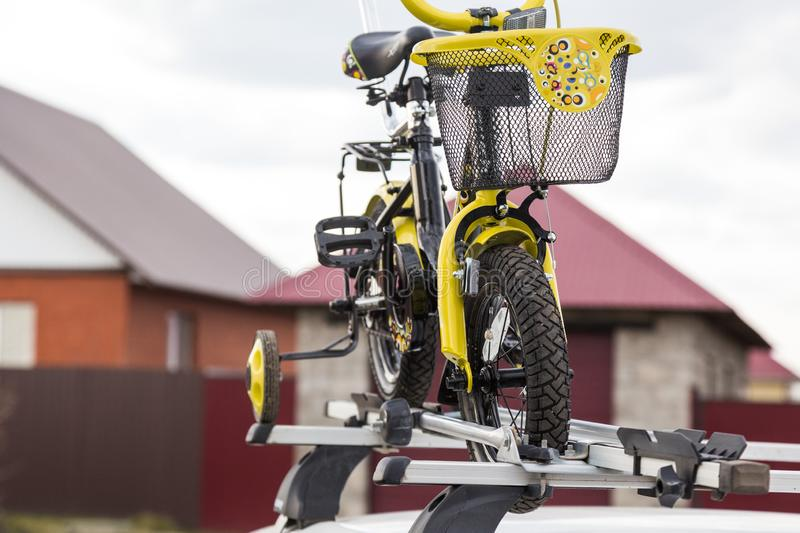 Bicycle transportation - a children`s bicycle on the roof of a car against the sky in a special mount for cycling. The. Bicycle transport - a children`s bicycle stock images