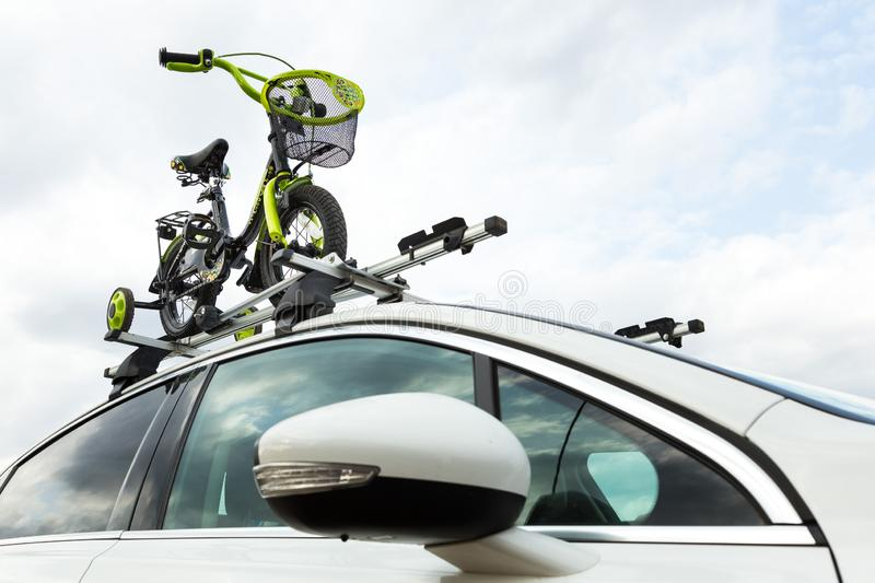 Bicycle transport - a children`s bicycle on the roof of a car against the sky in a special mount for cycling. The. Decision to transport large loads and travel stock image
