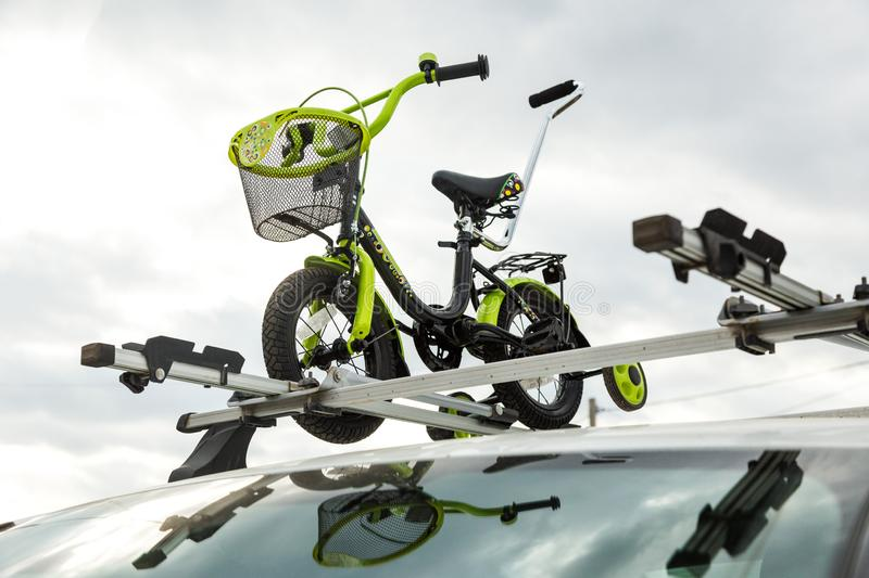 Bicycle transportation - a children`s bicycle on the roof of a car against the sky in a special mount for cycling. The. Bicycle transport - a children`s bicycle royalty free stock image