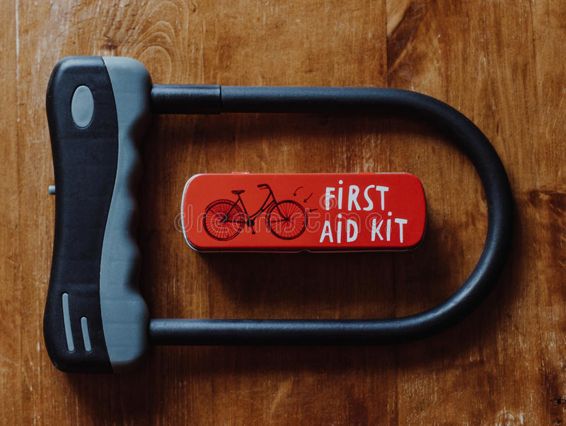Bicycle U shaped lock and bicycle repair kit. On wooden background royalty free stock images