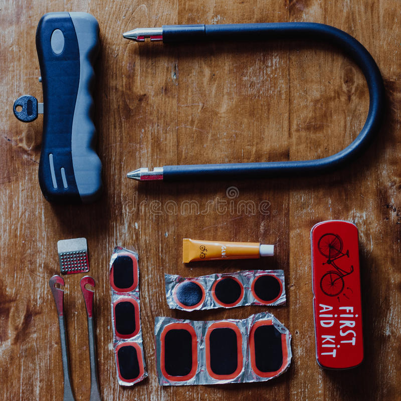 Bicycle U shaped lock and bicycle repair kit. On wooden background. Top view royalty free stock photo
