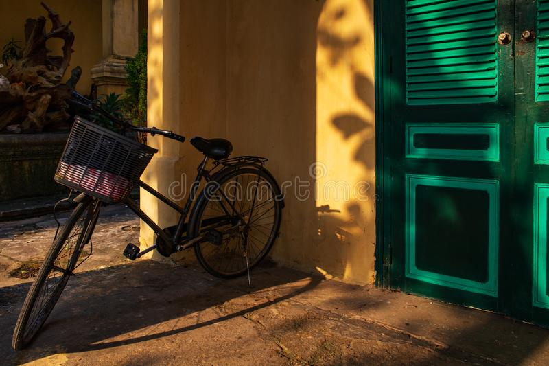 Bicycle in a veranda by a yellow wall with green doors with sun light rays. Shot in Thang Long Citadel, Hanoi, Vietnam. Bicycle in a veranda by a yellow wall stock image