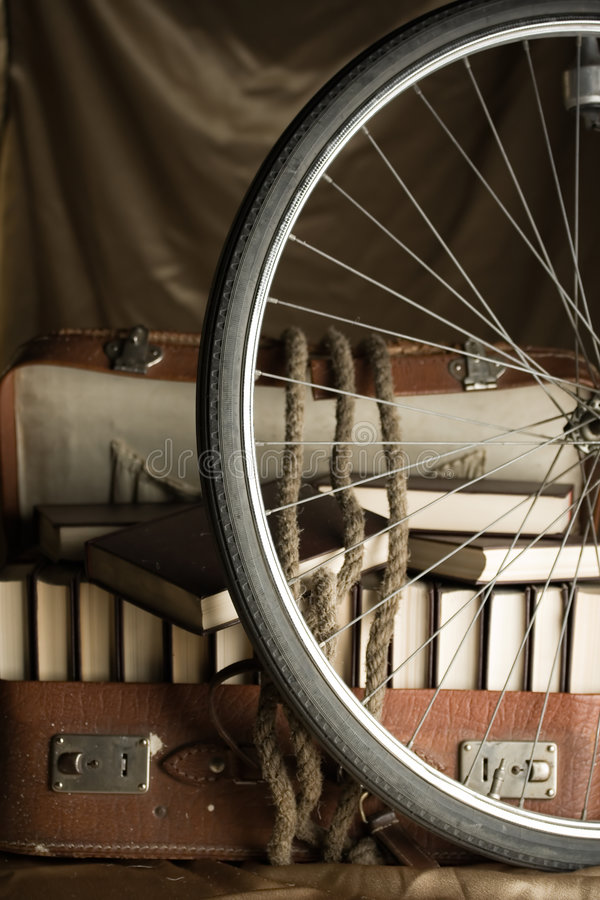 Bicycle wheel and old torn suit-case full of books royalty free stock photography