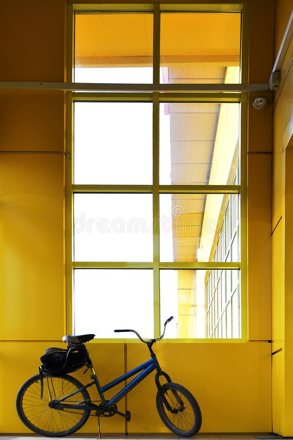 Bicycle by the window in a yellow building. stock image