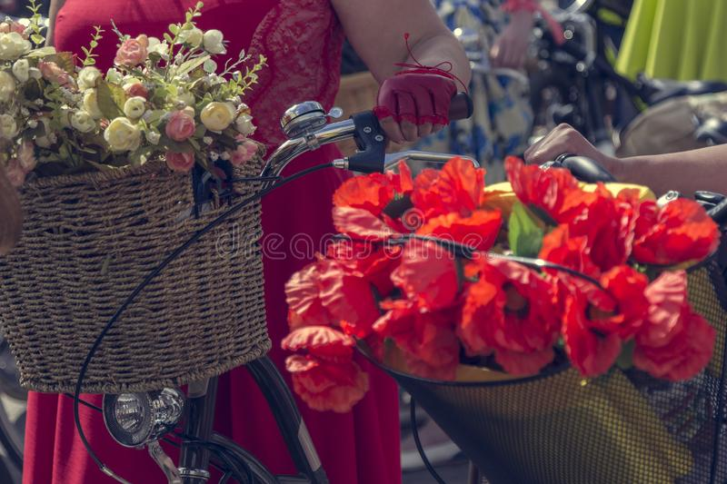 Bicycles with baskets of flowers. Woman in red skirt holds the handlebar.  royalty free stock photos