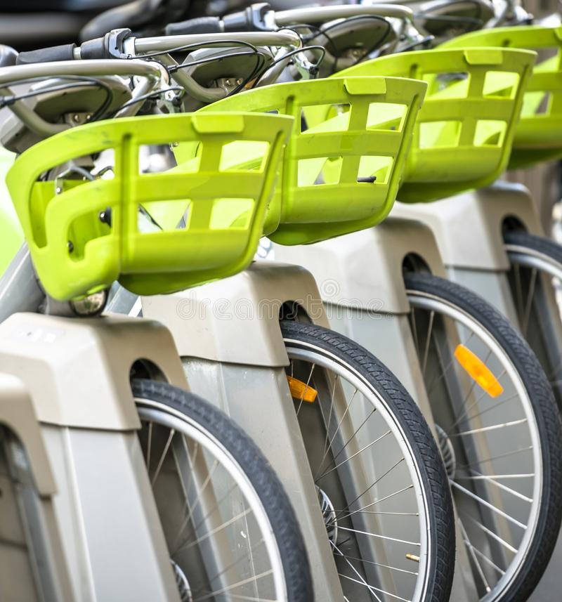 Bicycles with baskets for public rental stand at parking station in the row. Street transportation green public rent bicycles with basket for traveling around stock photography