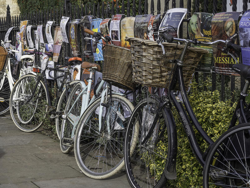 Bicycles chained up against a metal railed fence. Bikes chained to a metal railed fence with flyers pinned to it stock images
