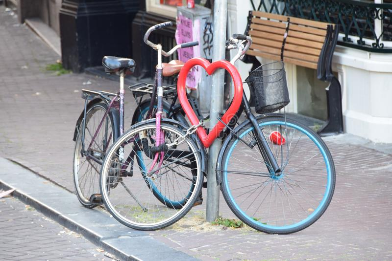 Bicycles chained up to a heart in Amsterdam. Love bicycle stand in Amsterdam.  Two bicycles chained up to it royalty free stock image