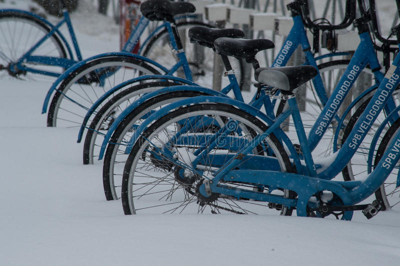 Bicycles covered with snow. Saint-Petersburg, Russia - November 8, 2016: Snowfall in the city streets. Bicycles covered with snow stock images