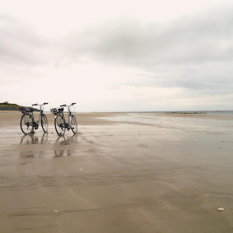 2 Bicycles on a flat beach on Il de Re South West France. 2 touring Bicycles on a flat beach under a grey sky on Il de Re South West France royalty free stock photo