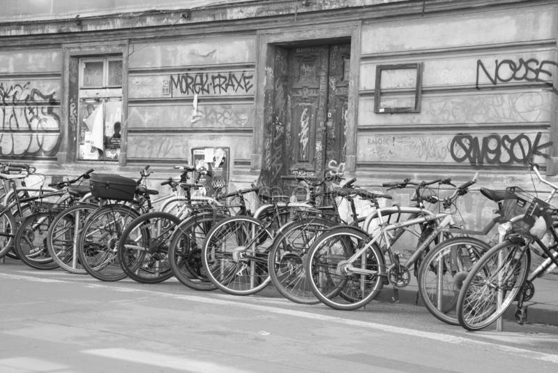 Bicycles grunge city graffiti. Bicycles locked up on city sidewalk in front of graffiti on wall in black and white royalty free stock images