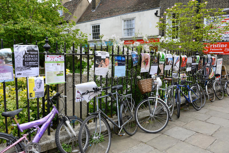 Bicycles Locked Up Along Fence in Cambridge. Row of Bicycles Locked Up Along Iron Fence Covered with Advertisement Posters, Cambridge, England stock images