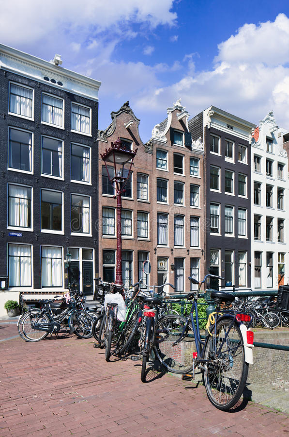 Bicycles parked against a rail with renovated ancient mansions, Amsterdam, netherlands stock photography