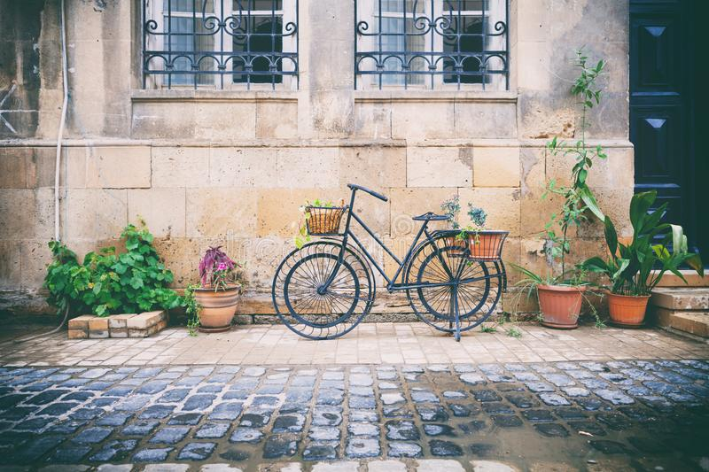 Bicycles parked near stone brick wall of old house among plants in pots in Icheri Sheher, Baku, Azerbaijan royalty free stock image