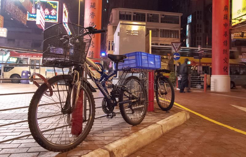 Bicycles parked on Temple Street next to gateway to Night Market, the famous night flea market in Hong Kong. royalty free stock photography