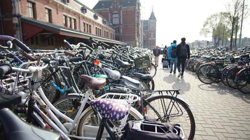 Bicycles parking in front of Amsterdam main station with tourist walking stock photos
