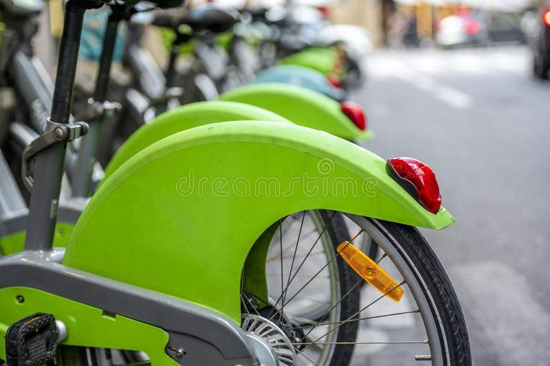 Bicycles for public rental use at parking station in row on city street. Street transportation green hybrid public rent bicycles for traveling around the Paris royalty free stock photography