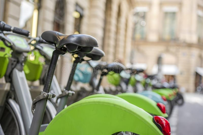 Bicycles for public rental use at parking station in row on street of Paris. Street transportation green hybrid public rent bicycles for traveling around the stock photo